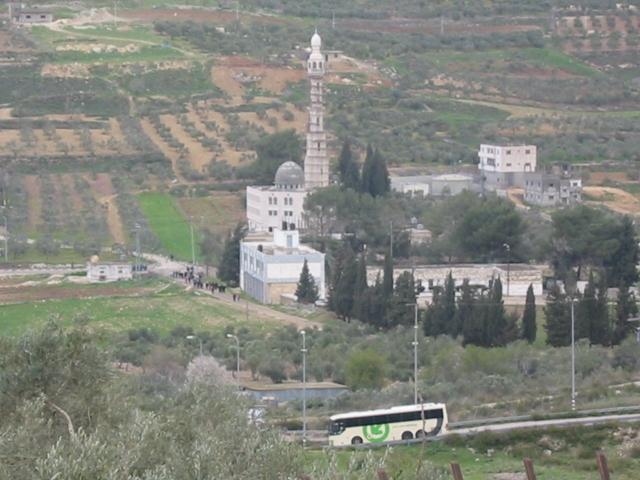 El autobus de uso exclusivo de Yitzhar desciende por la carretera también de uso exclusivo de los colonos, pasando frente a una de las mezquitas de Burin