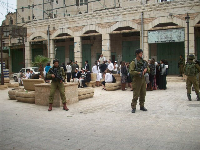 Soldados cuidando el paseo de los sábados de los colonos en Hebrón, donde la colonia israelí se estableció en el centro mismo de la ciudad (L. Foell)