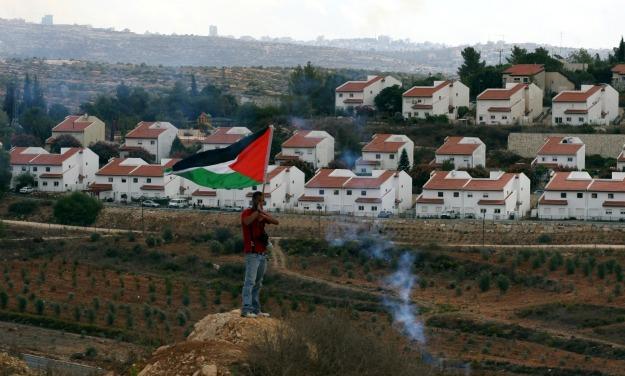 Poblador de Nabi Saleh manifestando. Detrás, la colonia israelí ilegal Hamish, que ha robado las tierras de la aldea palestina