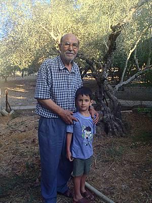Yusef con su nieto. Los árboles quemados estaban cerca de la carretera usada por los colonos. El equipo del EAPPI no pudo acercarse por temor a ser atacados (M.Collins).
