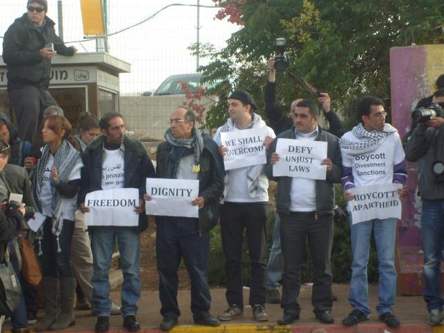 Lxs 6 activistas esperando para abordar el autobús prohibido en la estación de la colonia israelí Kokhav Ya'akov