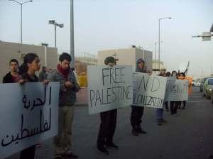 Manifestantes con carteles contra la ocupación en el checkpoint de Jerusalén