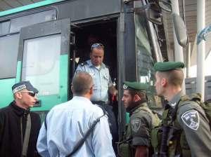 Policías y soldados desconcertados  ante la llegada del autobús al checkpoint de Jerusalén