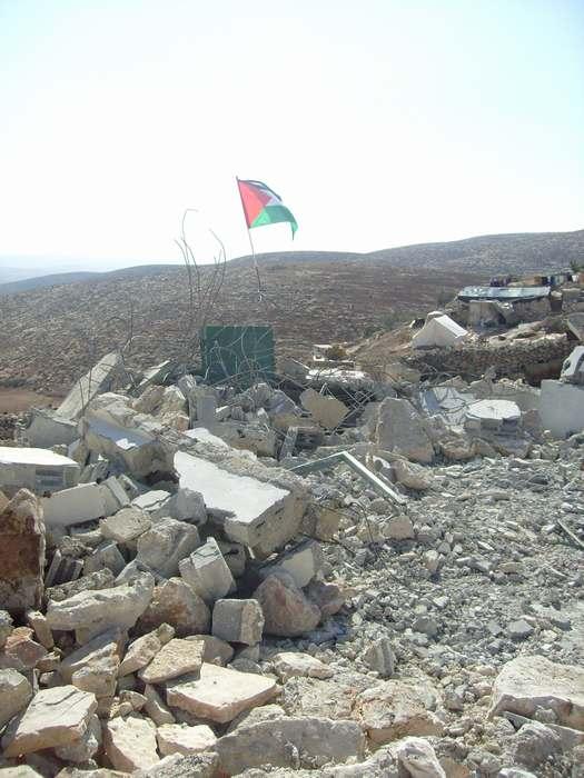 La bandera palestina flamea sobre los escombros de la casa demolida.