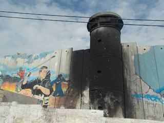 Una de las torres de vigilancia incendiada y el Muro perforado como acciones de resistencia en Aida