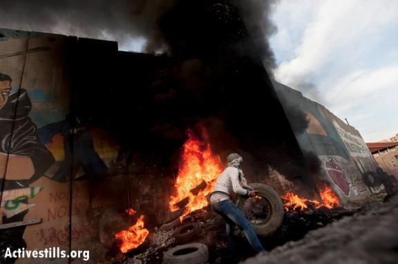 Prendiendo fuego a una de las torres del Muro en Belén (Ryan Rodrick Beiler)