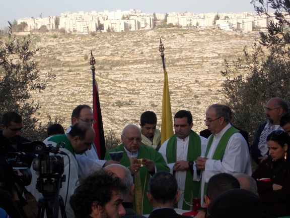 Misa en las tierras del monasterio de Cremisan (Belén), amenazadas por la expansión del Muro y las colonias israelíes ilegales (al fondo).