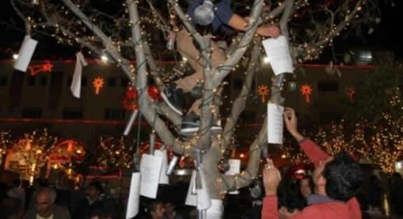 """Uno de los árboles en la Plaza del Pesebre 'decorados' por activistas de Belén con cartuchos de gas lacrimógeno """"made in USA"""" (PNN)."""