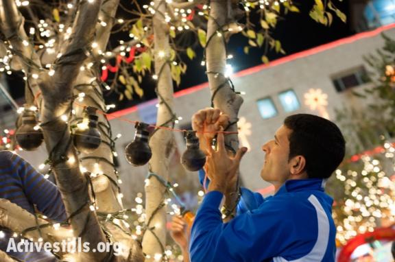 """Activistas locales 'decorando' un árbol en la plaza de Belén con granadas de gas lacrimógeno """"made in USA"""" (Ryan Rodrick Beiler)."""