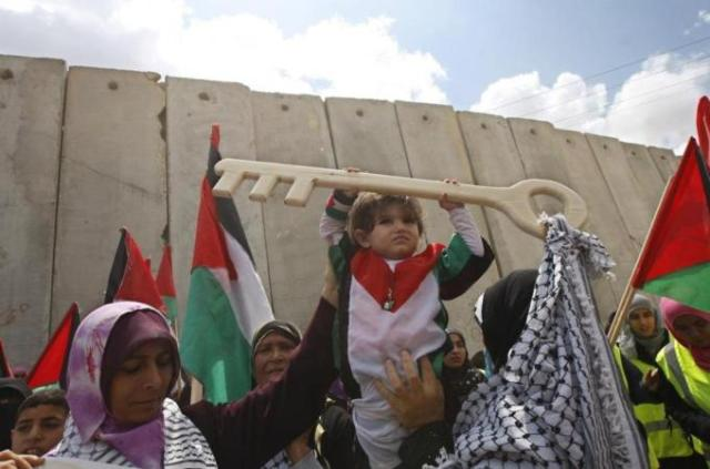Palestinas alzando símbolos de las llaves de los hogares de los que fueron expulsadas en 1948 (AFP)