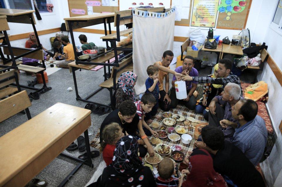 Una familia comparte el iftar (comida al final del día de ayuno de Ramadán) en una escuela de la UNRWA donde se refugió en ciudad de Gaza. (Wissam Nassar, NYT).