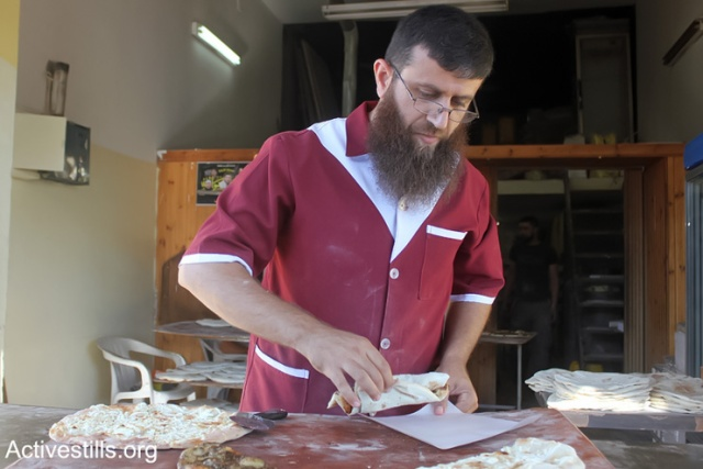 The Palestinian former prisoner Khader Adnan works at his bakery in the West Bank Village of Qabatiya near Jenin, June 21, 2013.