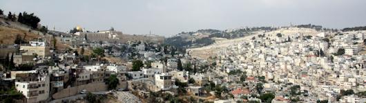 Las murallas de la Ciudad Vieja de Jerusalén con las cúpulas de las dos mezquitas, el Monte de los Olivos al medio, y Silwan (a la derecha).