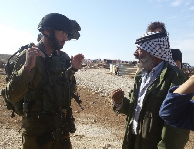 Abu Sakr hablando con los soldados después de la segunda demolición de su hogar en dos días (Lioy).