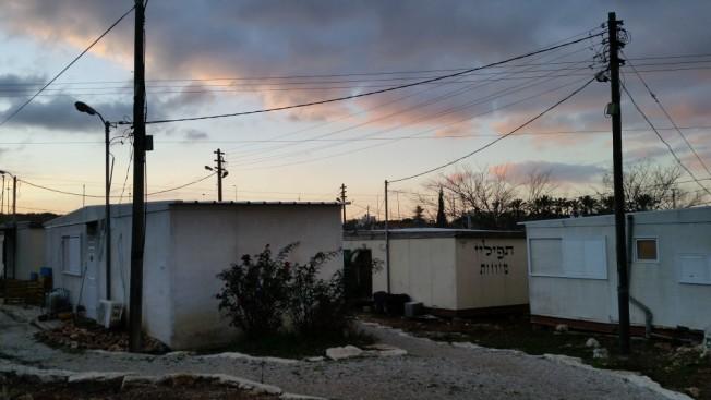 Módulos para alojar a los recién llegados a la colonia Ofra, en Cisjordania. Un cartel ofrece a la venta artículos religiosos.