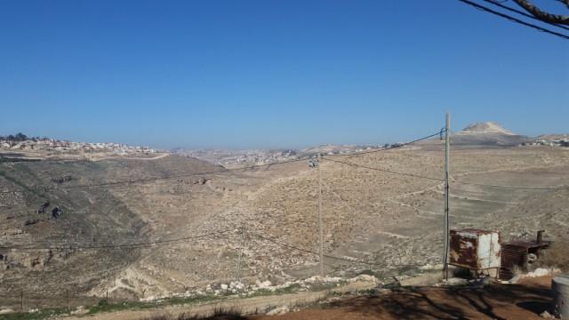 Vista norte desde la colonia Nokdim en el bloque Gush Etzion. La colonia Tekoa está a la izquierda. Al centro en primer plano hay una cámara de seguridad; al fondo a la derecha, el Herodium.