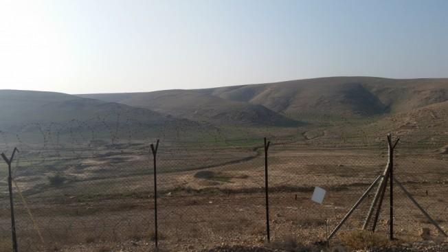 Vista al oeste desde el kibutz Na'aran en el Valle del Jordán. Más allá de la valla de seguridad está el valle y las colinas de Judea.