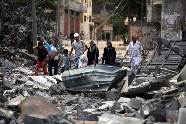 Una familia palestina camina entre los escombros de su vivienda destruida por Israel (foto de MEMO).