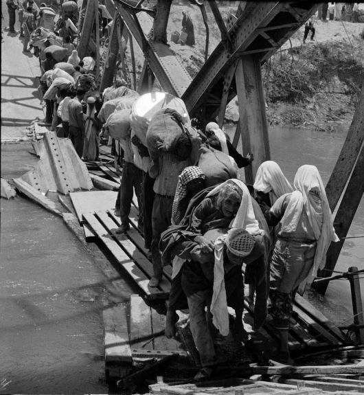 Refugiados palestinos huyen a través del río Jordán por el puente Allenby, dañado durante la guerra árabe-israelí de 1967.  (UNRWA archives)