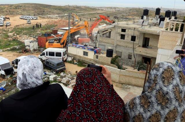 Mujeres palestinas observan la demolición de su vivienda en el barrio palestino Beit Hanina, en febrero de 2013. (WAFA).
