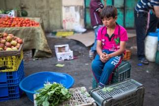 Un niño vende vegetales en el mercado de Gaza.