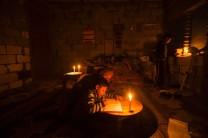 Escolar haciendo las tareas domiciliarias a la luz de una vela.