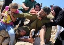 Ahed, su madre y su tía intentando evitar que un soldado arreste a su hermano en Nabi Saleh, el 28/8/15 (AFP).