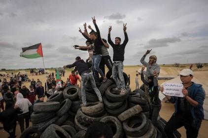 Juntando neumáticos para prenderlos fuego ante la valla israelí.