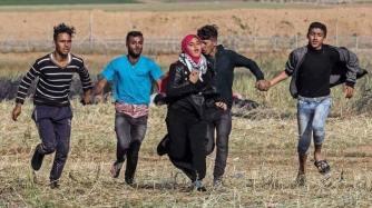 Jóvenes se toman de las manos para proteger a una compañera mientras huyen de las balas israelíes.