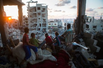 Una familia palestina contempla la salida del sol desde las ruinas de su hogar destruído en el barrio at-Tuffah, en Gaza, durante la operación Margen Protector (21/9/2014, Anne Paq, Activestills.org).