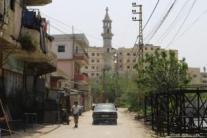 Dos niñas asoman la cabeza mientras el coche de su familia conduce por una calle del campo de refugiados de Nahr Al-Bared.