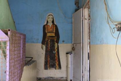 Dibujo de una mujer con traje tradicional palestino pintado en una pared en las afueras de Nada, una ONG que fomenta el bordado tradicional palestino.