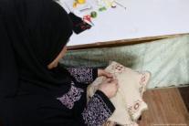 Una mujer palestina borda en tela un tapiz tradicional palestino que luego será vendido.