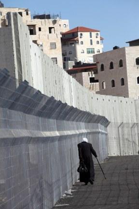 Una mujer palestina cruza el checkpoint instalado por Israel en el campo de refugiados de Shu'fat, a pesar de encontrarse dentro de los límites de Jerusalén (27/12/2011, Anne Paq, Activestills).