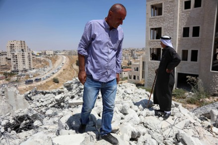 Palestinians stand on the rubble of a building demolished by Israeli forces on the outskirts of occupied East Jerusalem on 22 July.