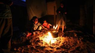 Una familia prepara la cena sobre el fuego debido a la escasez de combustible causada por el bloqueo israelí (Ashraf Amra/Al Jazeera).