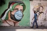 Un niño palestino camina ante un mural pintado en una pared en Rafah, Gaza, como parte de una campaña de concienciación sobre el COVID-19 (Abed Rahim Khatib/Flash90).