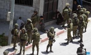 Fuerzas israelíes detienen a Khaled Abu-Baker (13) y lo hacen arrodillarse (al centro) en Yabad (12/5/20, Jaafar Ashtiyeh/AFP).