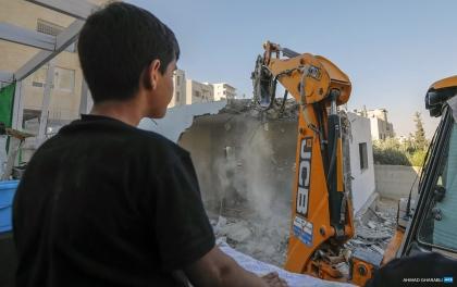 Un niño palestino observa la auto-demolición de su hogar con una excavadora contratada por su familia por órdenes israelíes en el barrio Al-Tur de Jerusalén Este (2/7/20, Ahmad Gharabli/AFP).
