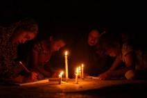 Niñxs palestinxs hacen la tarea escolar a la luz de las velas debido a la falta de electricidad debido al bloqueo israelí en Khan Yunis, Gaza (agosto 2020, Mohammed Zaanoun).