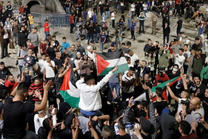 Palestinian protesters raise national flags as they gather near the Damascus Gate in Jerusalem's Old City, Palestinos protestan en la Puerta de Damasco, Ciudad Vieja de Jerusalén. 25/4/21 (Ahmad GHARABLI/AFP)