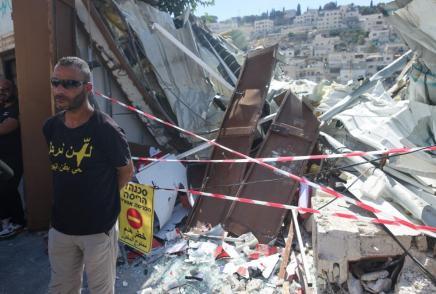 """Un hombre con una camiseta con la leyenda """"No nos iremos"""" junto a las ruinas de su comercio demolido por las autoridades en Al-Bustan, Silwan. 29/6/21. (AFP)"""