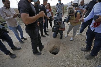 Policías y periodistas observan la salida del túnel subterráneo por donde escaparon los seis prisioneros (AFP).